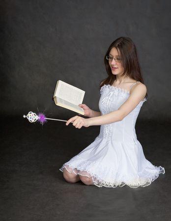 esoterismo: La ni�a - de hadas con una varita m�gica y el libro en las manos de Foto de archivo