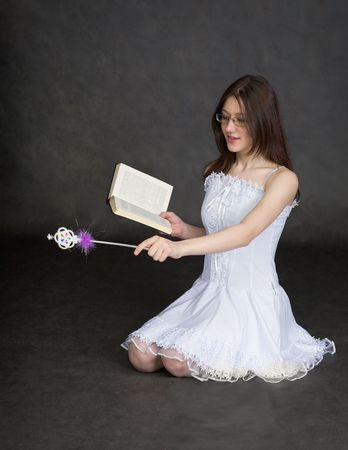exorcism: The girl - fairy with a magic wand and the book in hands Stock Photo