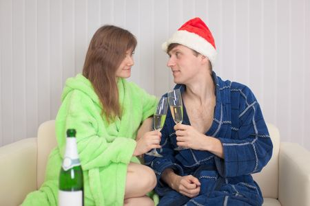 dressing gowns: The young couple drinks sparkling wine sitting on a sofa in dressing gowns
