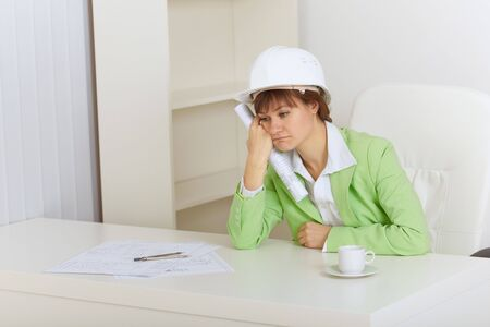 superintendent: The woman the construction superintendent sits upset for a table