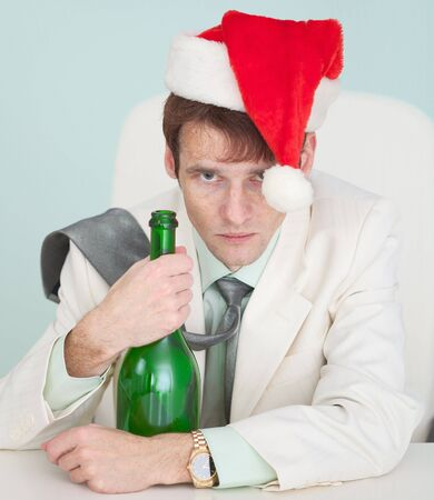 The drunk and tired guy in a white jacket with a bottle celebrates Christmas photo