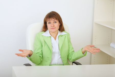 The surprised businesswoman shrugs at a office photo