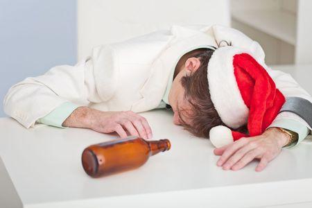 La persona borracha en un gorro de Navidad se encuentra sobre una mesa blanca  Foto de archivo - 5889297