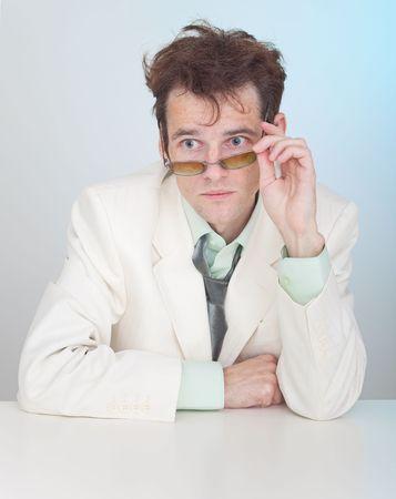 zerzaust: Der Mann mit dem zerzaustem Haar sitzt an einem Tisch Lizenzfreie Bilder