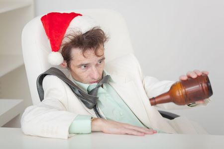 necktie and beer: The drunken person in a Christmas cap with a bottle in a hand