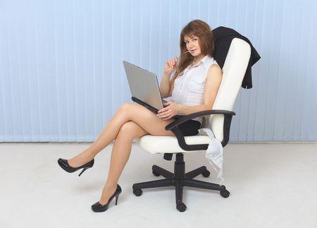 secretaria sexy: La joven sexual - Secretario se sienta en un sill�n con el port�til  Foto de archivo