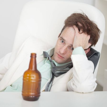 necktie and beer: The person suffers from a hangover sitting at a table