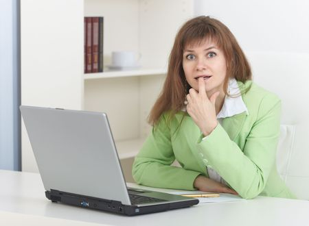The young woman sits at a table at light office with the laptop Stock Photo - 5933627