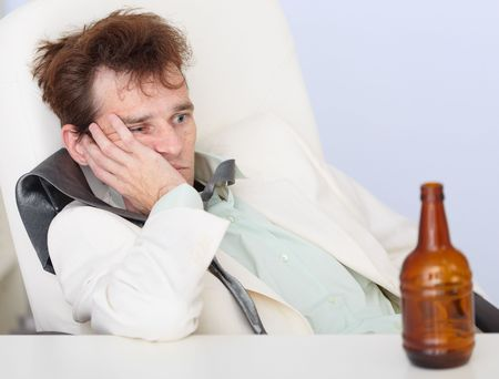 necktie beer: The young businessman sits sad with an empty bottle