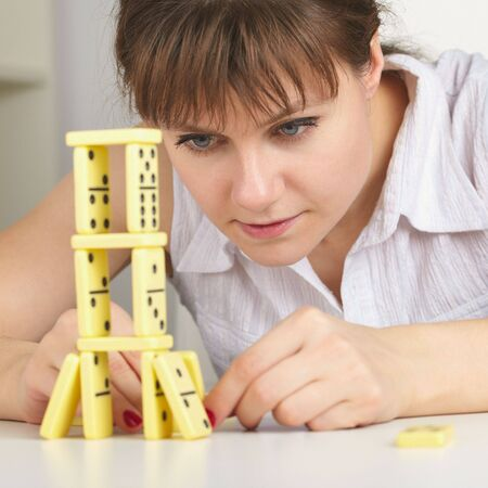 accurately: The young woman accurately builds a tower of dominoes