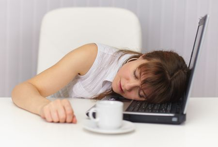 The young girl sleeps having placed a head on the laptop keyboard Stock Photo - 5943905