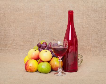 Still-life from a red bottle and fruit against a canvas Stock Photo - 5954239