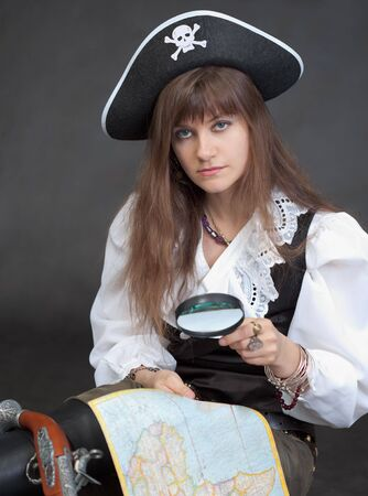 The woman - the sea pirate with a map and a magnifier Stock Photo - 5943938