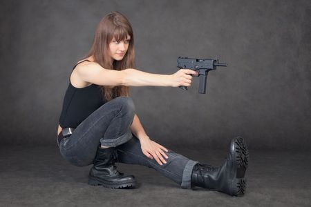 The young woman shoots from a pistol sitting on one leg photo