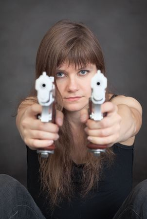 The young serious woman aims from two pistols photo