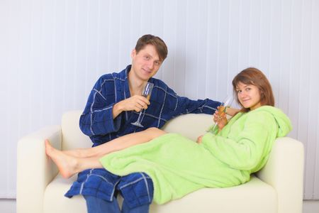 dressing gowns: The young couple drinks sparkling wine on a sofa in dressing gowns Stock Photo