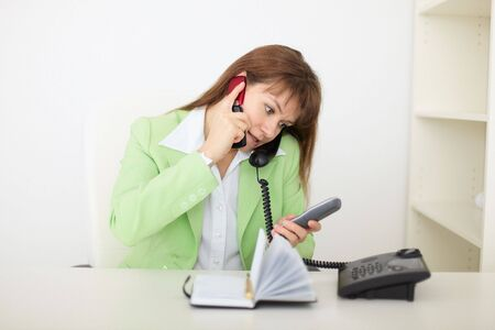simultaneously: The beautiful woman - the secretary speaks by several phones simultaneously Stock Photo
