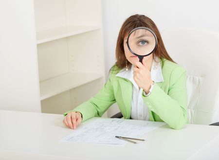 The young woman sits at a table with the big magnifier in hands photo
