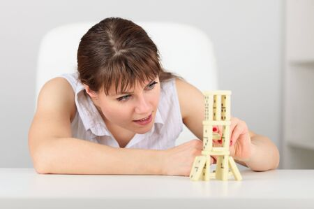 accurately: The young woman accurately collects a construction from dominoes