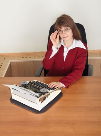 Woman in spectacles working with old typewriter at office photo