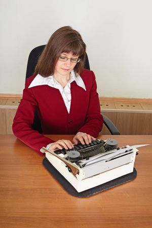 The woman prints on an ancient typewriter sitting at a table photo