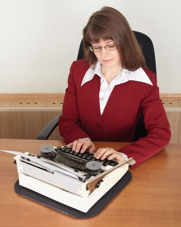 The young woman works with a typewriter photo