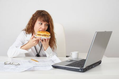 The person at office on a workplace eats a hamburger photo