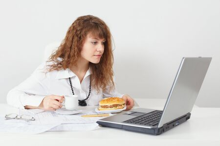 The young beautiful woman was going to eat behind a table at office photo
