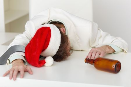 necktie beer: Strongly drunk man in a Christmas cap lies on a table at office