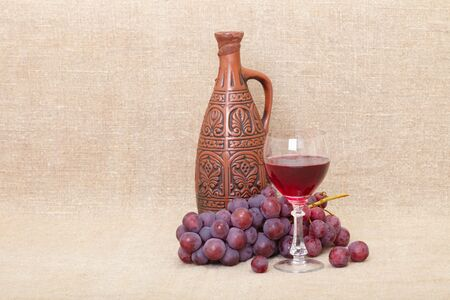 Art composition from a clay large bottle, grapes and a glass Stock Photo - 6051406