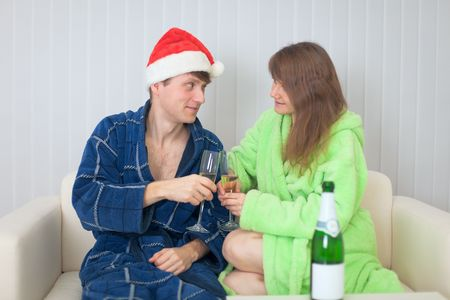The young couple drinks sparkling wine in dressing gowns on a sofa photo
