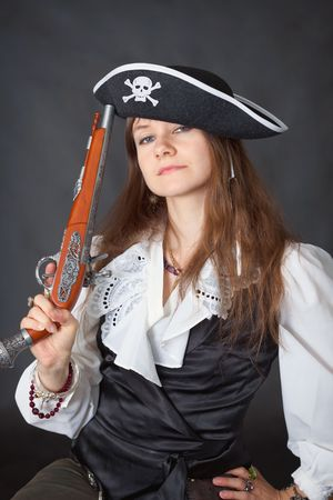 ancient sexy: Portrait of the beautiful girl in a pirate hat with an ancient pistol in a hand