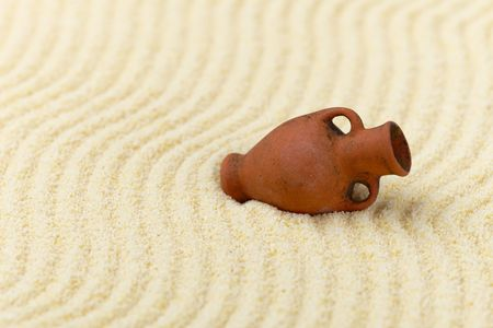 mellow: The ancient clay amphora lies on a surface of yellow sand