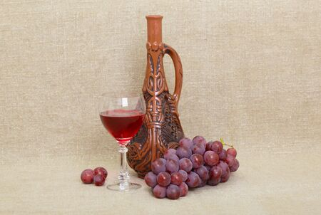 Composition from clay Georgian bottle, a glass and grapes against old canvas Stock Photo - 6095264