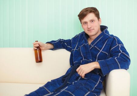 dressing gown: The young man drinks beer in a dressing gown on a sofa