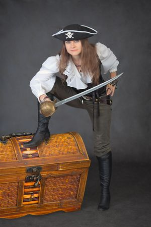 The sea pirate with a sabre and the big chest of treasures photo