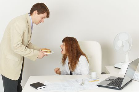 comically: The young woman comically reaches for meal at office during the lunchtime
