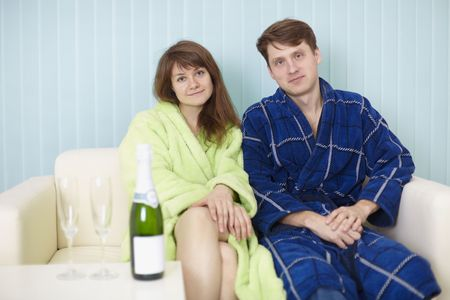 dressing gowns: Young happy couple in dressing gowns on sofa