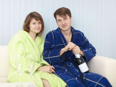 dressing gowns: Young happy couple in dressing gowns drinks sparkling wine Stock Photo