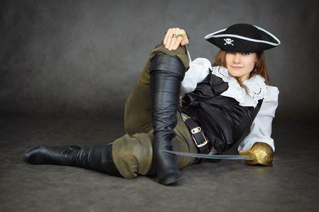 mujer pirata: La mujer insolente, el pirata se encuentra con un sable sobre un fondo negro Foto de archivo