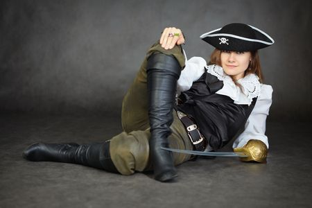pirate captain: The impudent woman the pirate lies with a sabre on a black background Stock Photo