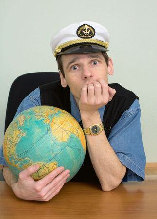 misses: The seaman misses on distant travel sitting at a table with the globe Stock Photo
