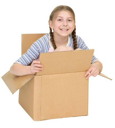The amusing little girl sits in a cardboard box isolated on a white background photo
