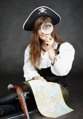 Woman pirate, and map with a magnifying glass sitting on a black background photo