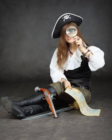 Girl pirate, and map with a magnifying glass sitting on a black background photo