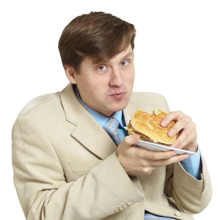 masticate: The funny young businessman eats a sandwich isolated on a white background