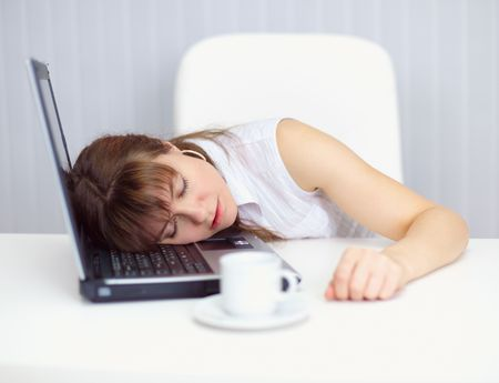 comically: Young woman comically asleep on the keyboard at the table Stock Photo