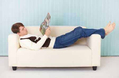 adult magazines: A young woman lies comfortably on a sofa with a magazine Stock Photo