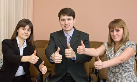 deliberation: Team of cheerful businessmen show thumb up