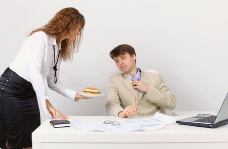 The secretary serves the Chief sandwich, in the workplace in the office photo